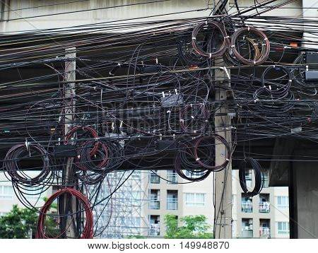 messy electric and telephone lines on poles in Bangkok Thailand