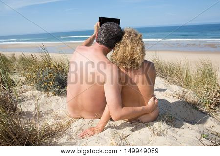 Relaxing nudist couple sitting on holidays at the sea