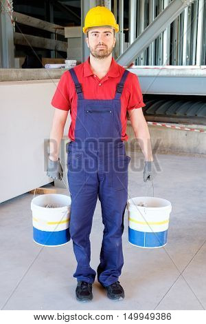Worker Holding Buckets In A Construction Site