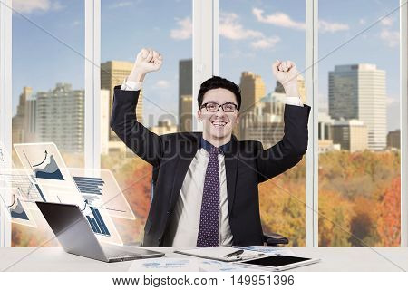 Photo of a successful Arabian entrepreneur raising hands in the office with virtual financial graph on the notebook computer