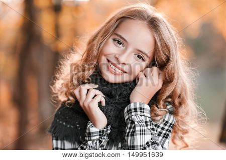 Autumn portrait of smiling blonde teen girl 13-14 year old wearing knitted scarf posing over yellow leaves outdoors. Looking at camera. Teenager hood.