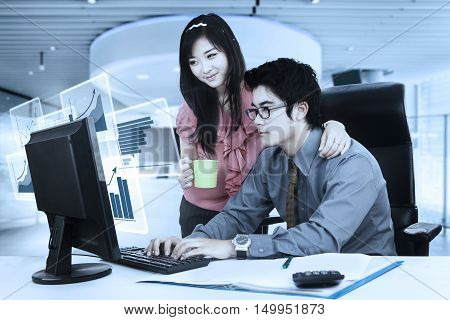 Two Asian businesspeople working in the office with virtual financial chart on the monitor