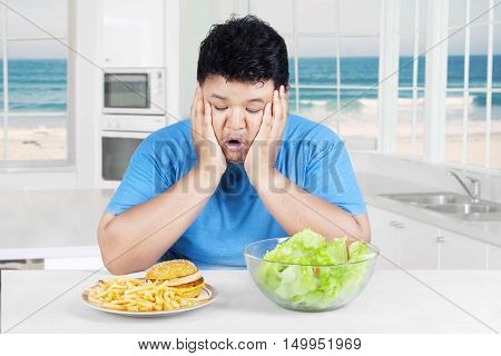 Picture of overweight Asian person sitting in the kitchen and looks confused while looking at salad and burger