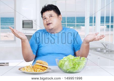 Overweight Asian person thinking to choose salad or hamburger shot in the kitchen at home