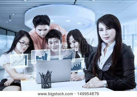 Young businesswoman smiling at the camera with her partners looking at virtual financial graph on the laptop shot in the office