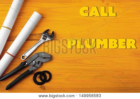 Call Plumber. Plumber tools and blueprints on yellow wooden background