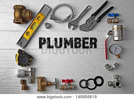 Plumbing concept. Plumber tools frame on white wooden background