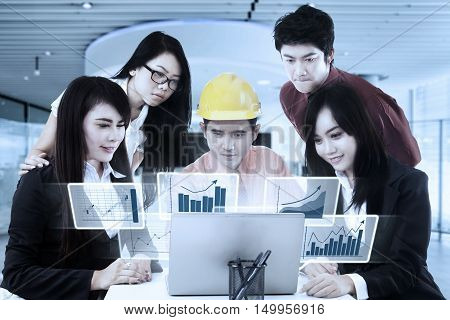 Businessman wearing hardhat and discussing with his partners while looking at virtual financial chart on laptop