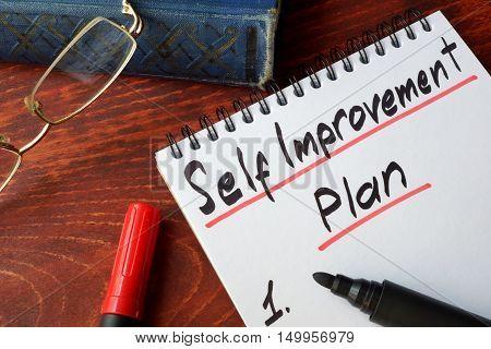 Self improvement concept written in a notepad.