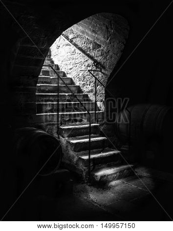 Old cellar staircase in low light - Dramatic black and white image with aged stone stairs going into an abandoned wine cellar with dark shadows and small beams of light.