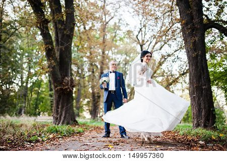 Stylish Brunette Bride Play With Dress On Autumn Path