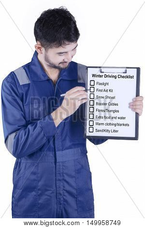 Image of a male mechanic wearing blue uniform and showing winter driving tips in the studio isolated on white background