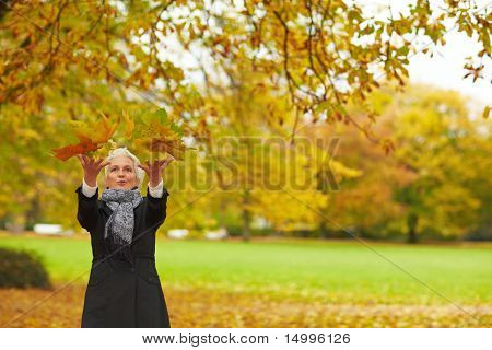 Senior Woman Throwing Maple Leaves
