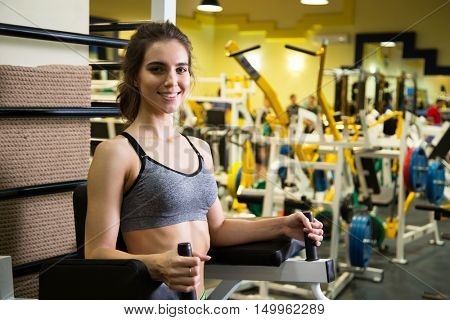 Fitness. Woman at the gym doing arms exercises on a machine