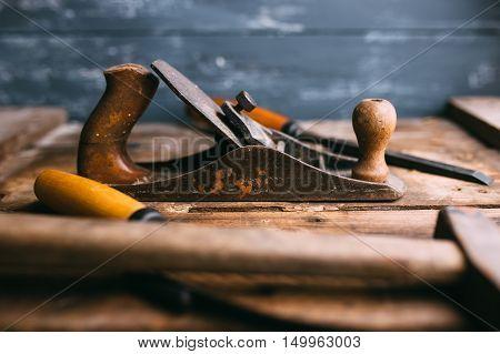 Old vintage hand tools on wooden background. Focus on jack-plane. Carpenter workplace