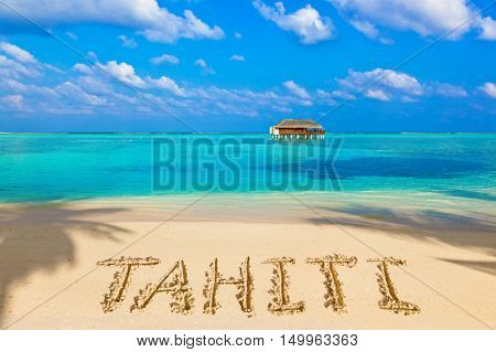 Word Tahiti on beach - concept holiday background