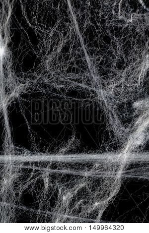 Cobweb or spider's web against a black background, to be used as overlay for Halloween designs