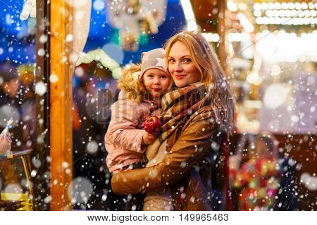 Beatiful mother and little daughter eating crystalized sugared apple on German Christmas market. Happy family in winter clothes with lights on background. Family, tradition, holiday concept