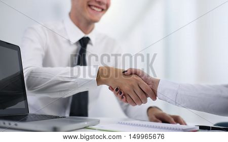 Two people shaking hands in the office