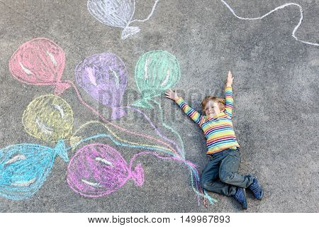 Adorable little kid boy having fun with colorful balloons picture drawing with chalks on ground. Creative leisure for children outdoors in summer, celebrating birthday, card invitation idea