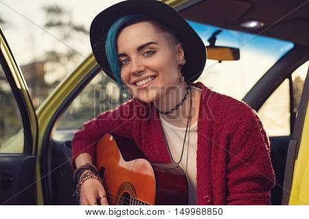 Closeup Face Portrait Of Folk Singer With Guitar In Car Outdoors