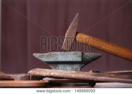 Old rusty rugged anvil hammer and other blacksmith tools on brown natural wooden background.