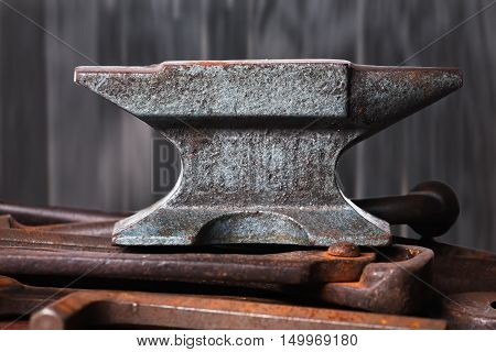 Old rusty rugged anvil on top of other blacksmith tools on black wooden background.