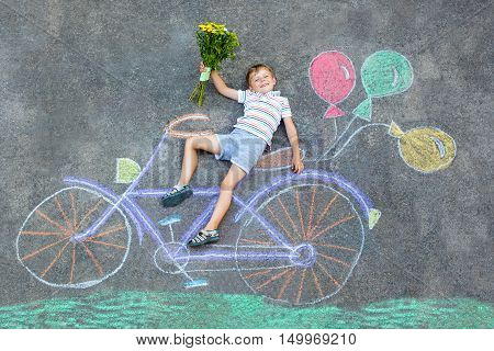 Happy little kid boy having fun with bicycle and air balloons picture drawing with colorful chalks on ground. Children, lifestyle, fun concept. funny child playing and dreaming. Birthday card