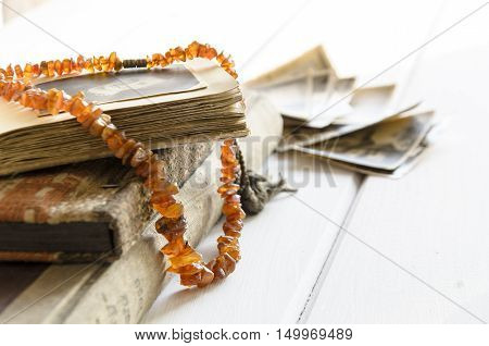 Stack of old photographs with amber necklace on photo album