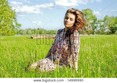 Relaxed Young Girl Sitting On Grass In Park - Outdoor