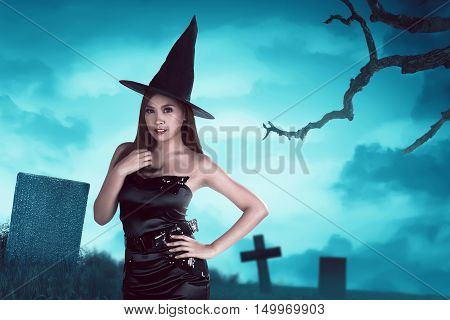 Young Asian Witch Woman With Hat Standing Around In A Cemetery