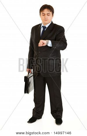 Serious businessman with suitcase looking at watch isolated on white
