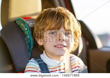 Portrait of little kid boy sitting in safety car seat. Happy child enjoying road trip and vacations. Safety concept