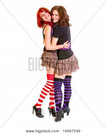 Two good girlfriends cheerfully embracing isolated on white