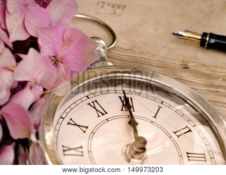 midnight on a vintage clock with pink flower petal and a foutain pen