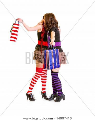 Two young girlfriends with shopping bags happy hugging isolated on white