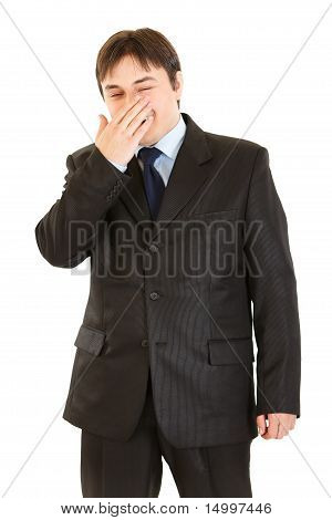 Laughing businessman closing his mouth by hand isolated on white