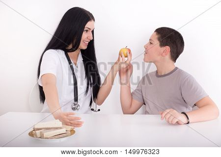 Female Doctor Offering Apple To A Boy
