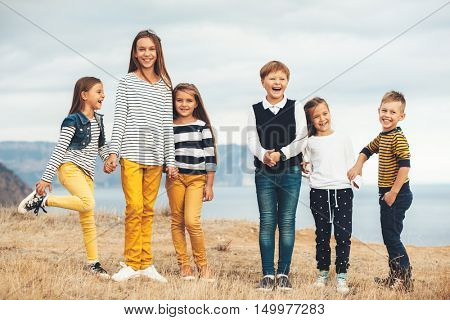 Group of fashion children wearing same style clothing having fun in the autumn field. Fall casual outfit in navy and yellow colors. 7-8, 8-9, 9-10 years old models.