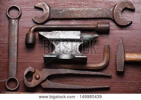 Old rusty rugged anvil and other blacksmith tools on brown natural wooden background. Flat lay top view.