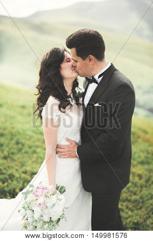 Beautifull wedding couple kissing and embracing near mountain with perfect view.