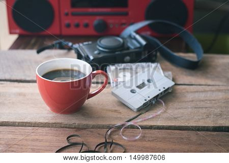 Cassette tape and red coffee cup with red radio on background.