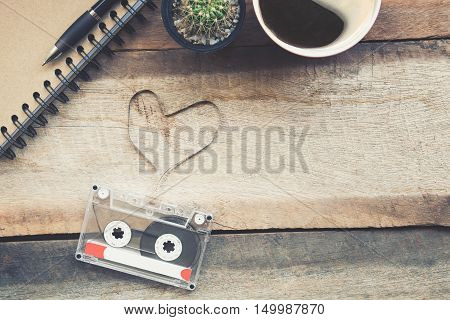 Cassette tapes shaping a heart on wooden table.vintage effect.