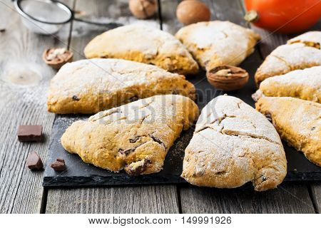Pumpkin scones with walnuts and chocolate for breakfast on a dark wooden background. Selective focus.