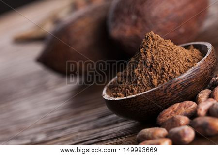 Cocoa beans in the dry cocoa pod fruit on wooden background