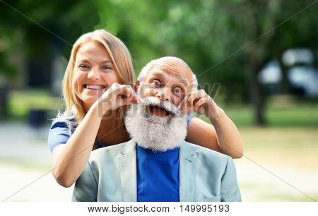 Grandfather and granddaughter sitting in a park