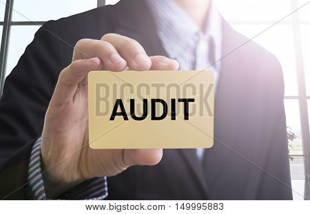 businessman hand holding a business card with a message audit for advertise concept.