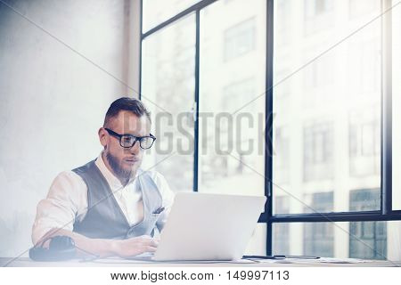 Stylish Bearded Businessman Wearing Glasses White Shirt Waistcoat Working Modern Office Startup Project.Creative Young Guy Using Laptop Computer Wood Table Workplace.Panoramic Windows Background