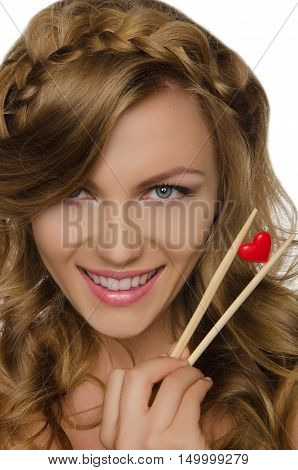 pretty woman holding heart with chopsticks isolated on white