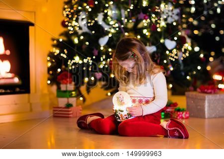 Family on Christmas eve at fireplace. Little girl opening Xmas presents holding snow globe. Child under Christmas tree with gift boxes. Decorated living room. Cozy winter evening at home.